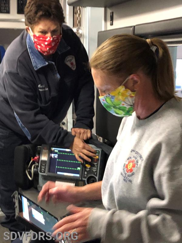 Assistant EMS Chief Carol Boehm and EMS Captain Kim Collins check out patient monitoring equipment while donning required infection control protective personal equipment.