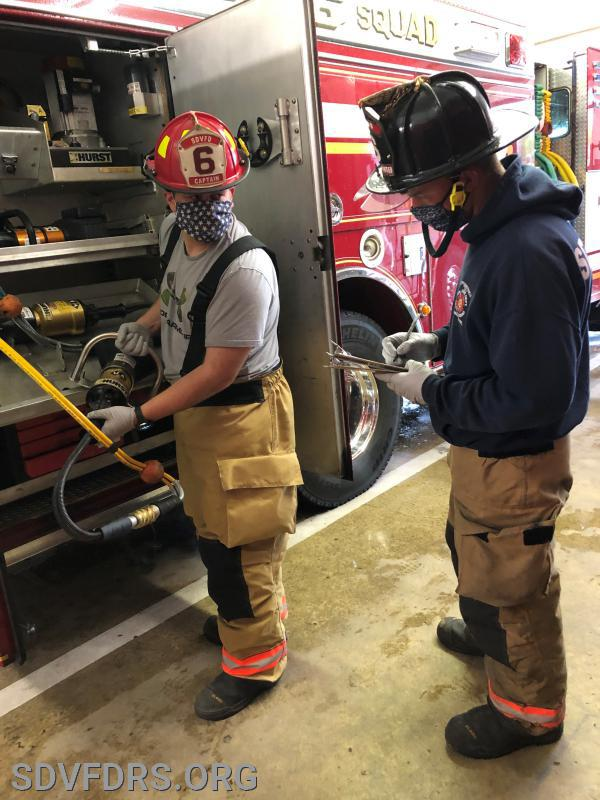 Fire Captain Ben Windsor and Firefighter Jason Hayden check out equipment on the fire apparatus, while donning required infection control protective personal equipment.