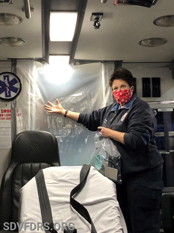 Assistant EMS Chief Carol Boehm points out some of the new, extraordinary infection control procedures now in place on the ambulances. The plastic sheeting is sealed and isolates the driver from the patient compartment, to protect the driver from possible infection. The used plastic is disposed of and replaced with a new piece after each call.