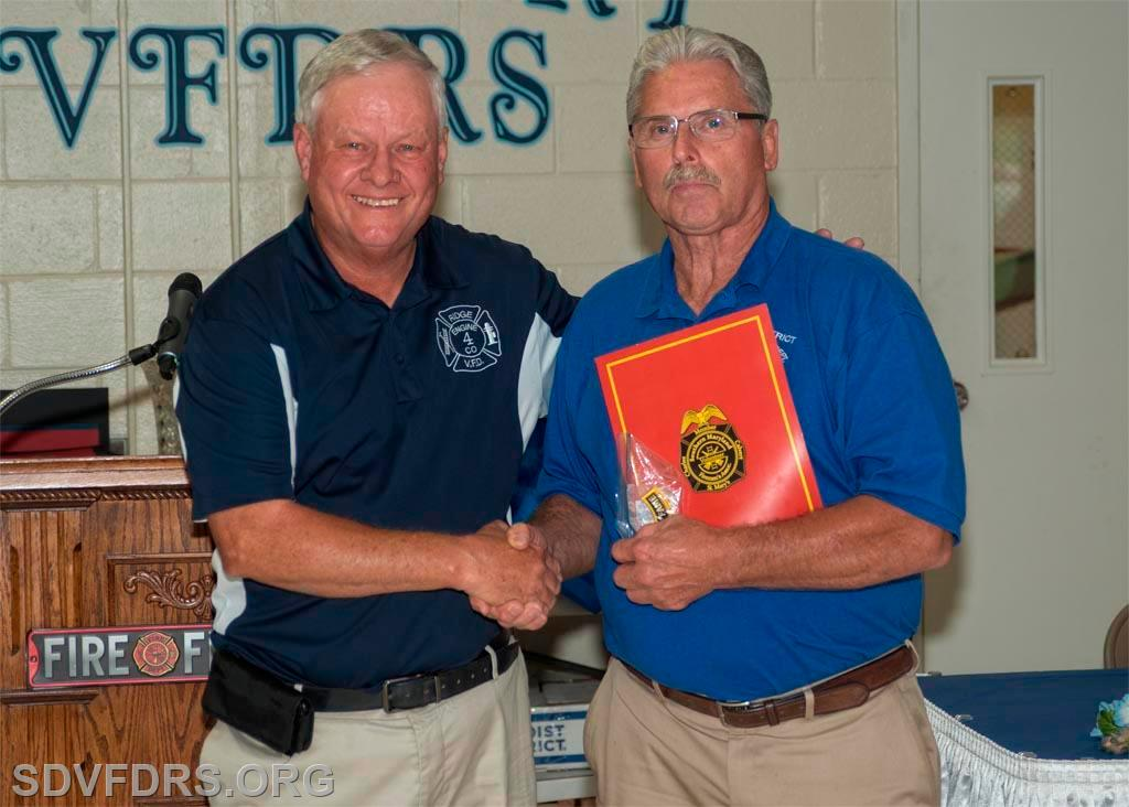 Keith Raley, SMVFA, presents Joseph V. Slade with certificates and ribbon signifying his induction into the Southern Maryland Volunteer Firemen's Association Hall of Fame for 2021.